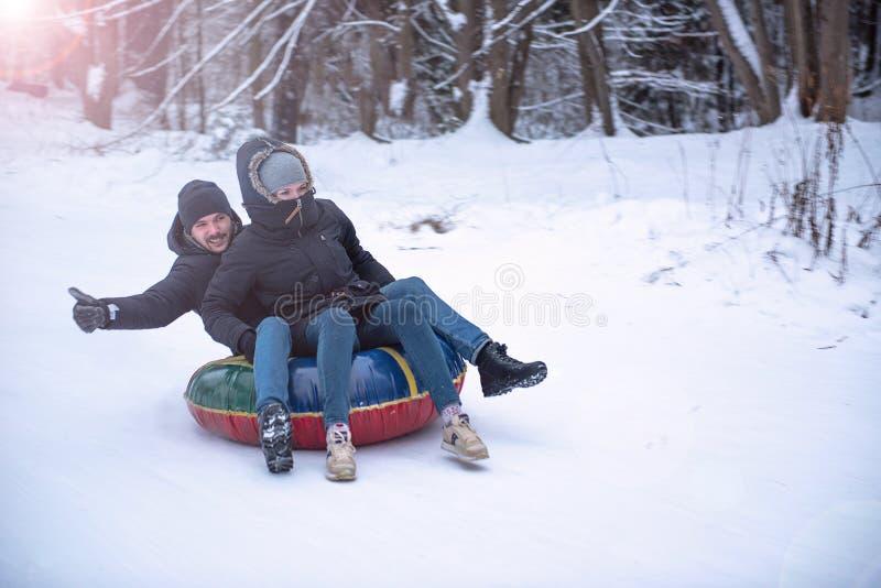 Giovane tipo e una tubatura dello sci della ragazza nel giro di inverno giù una collina immagine stock libera da diritti