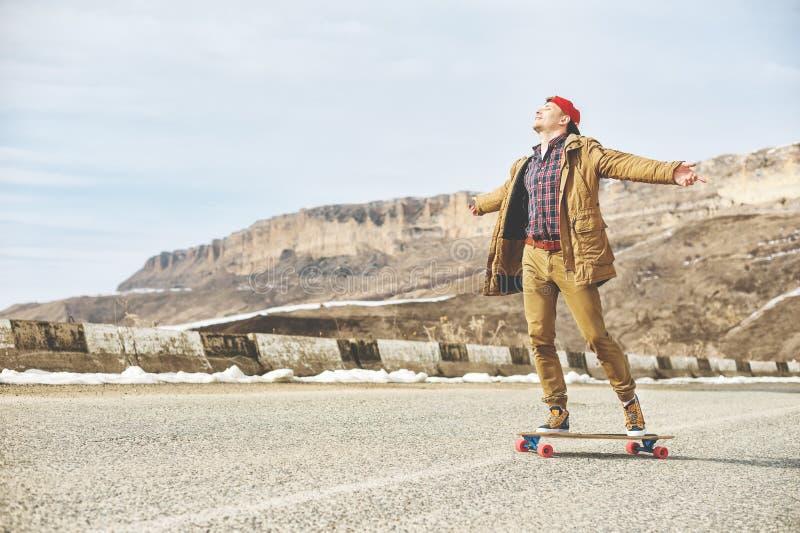 Giovane tipo felice alla moda in un cappuccio e nei pareggiatori dei pantaloni che rotolano giù una strada della montagna su un l fotografia stock libera da diritti