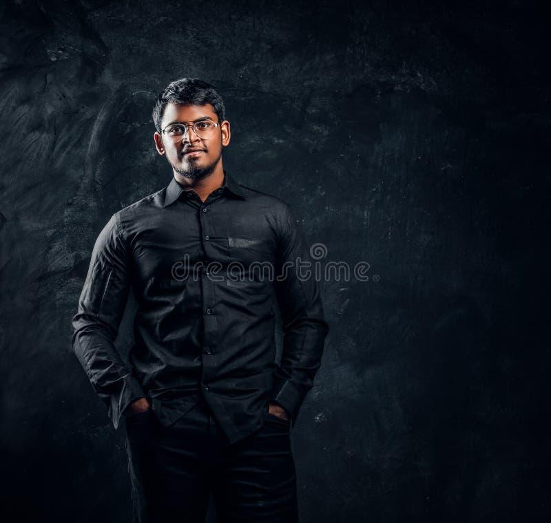 Giovane tipo indiano sicuro in vetri e camicia nera che posano per la macchina fotografica che si tiene per mano in tasche fotografie stock libere da diritti