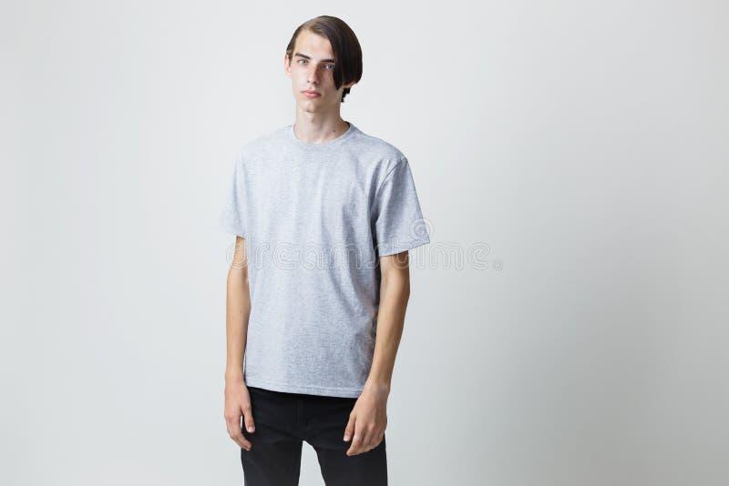 Giovane tipo moro sottile bello premuroso con gli occhi azzurri che indossano condizione grigia della maglietta contro grigio chi fotografia stock libera da diritti