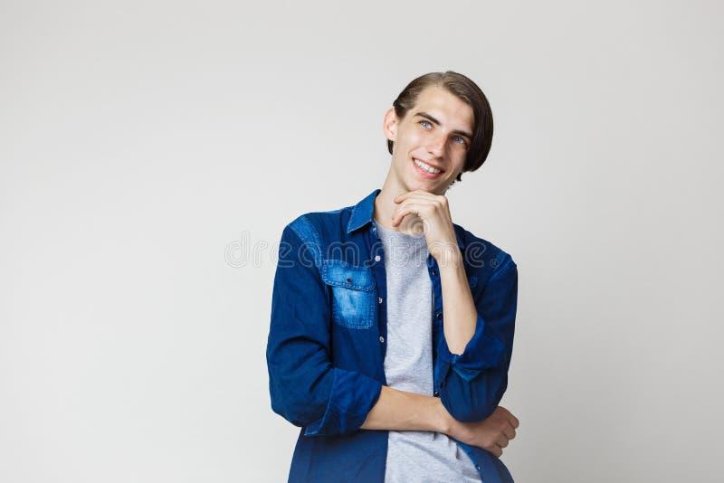 Giovane tipo moro sottile bello sorridente con gli occhi azzurri che portano la camicia blu del denim, guardando a sinistra e su, immagine stock libera da diritti