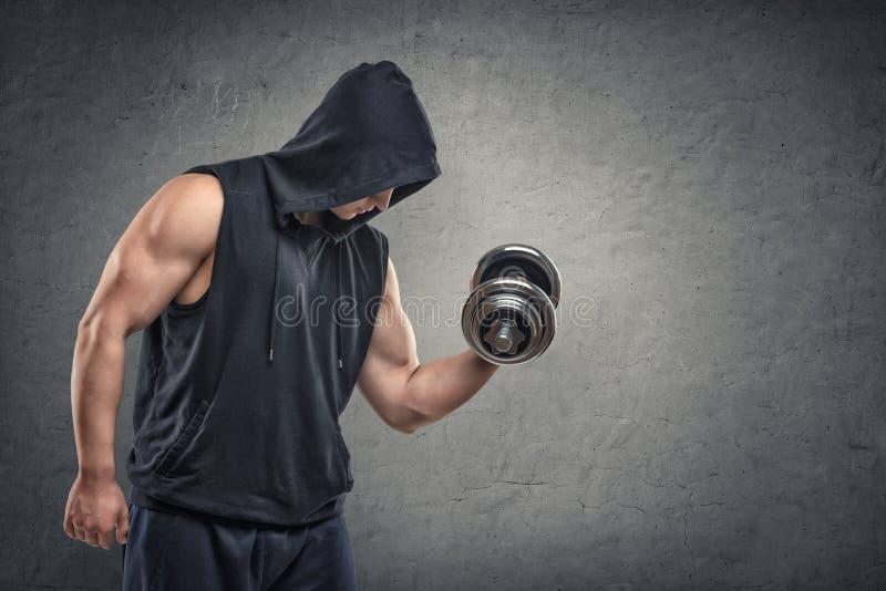 Giovane tipo muscolare in maglia con cappuccio che solleva una testa di legno per mostrare il suo bicipite fotografia stock