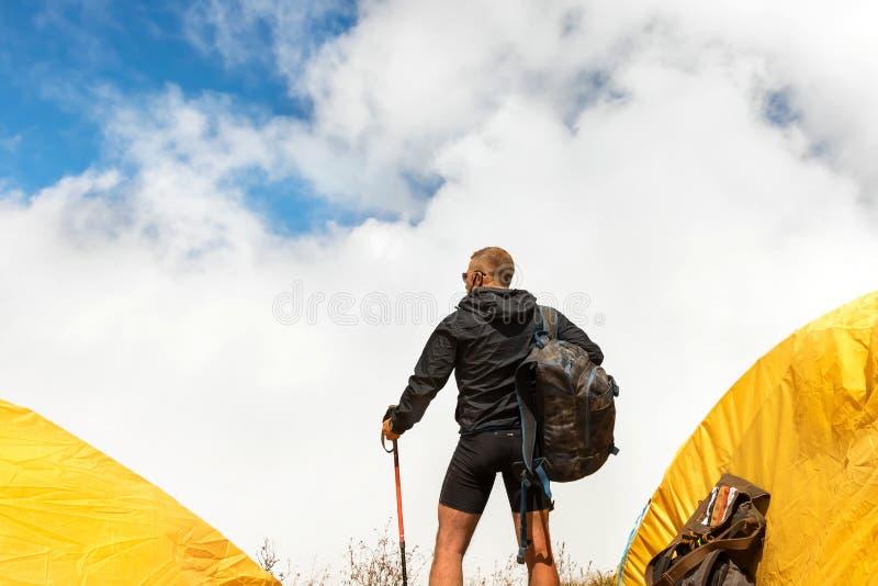 Giovane tipo sportivo con uno zaino in un campo della tenda che guarda lontano contro un fondo dei cumuli e di un cielo blu fotografie stock libere da diritti