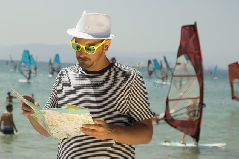 Giovane tipo turistico che esamina i surfisti del vento e della mappa stradale nei precedenti fotografia stock libera da diritti