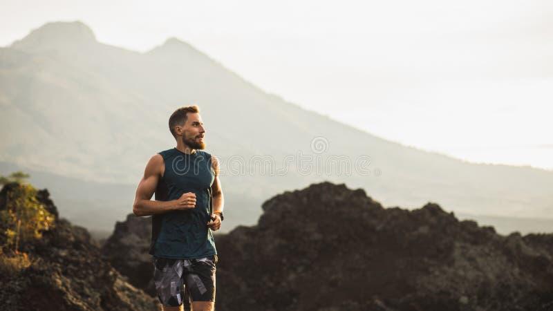 Giovane traccia dell'uomo dell'atleta che corre in montagne fotografia stock