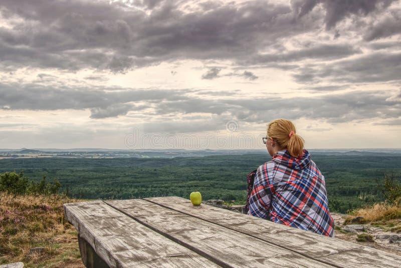 Giovane trekker biondo della ragazza che riposa alla tavola di legno fotografie stock
