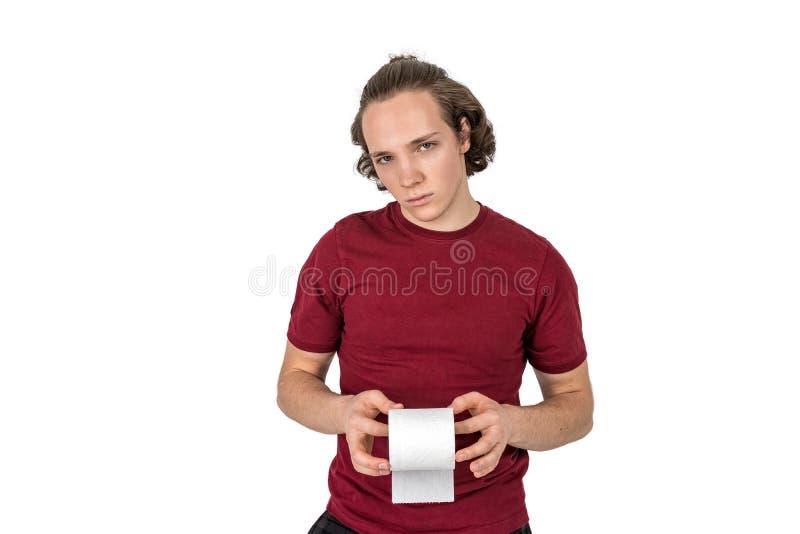 Giovane triste che giudica un singolo rotolo della carta igienica isolato su fondo bianco fotografia stock libera da diritti