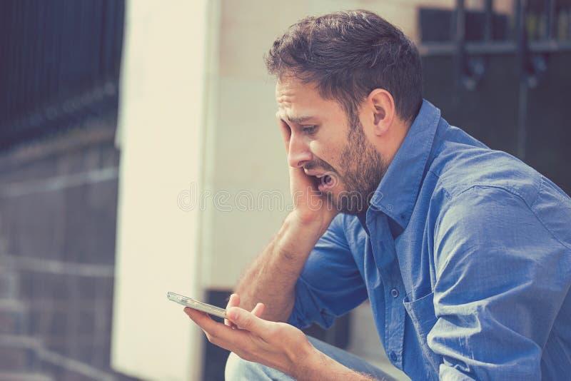 Giovane triste disperato che esamina cattivo messaggio di testo sul suo telefono cellulare immagine stock