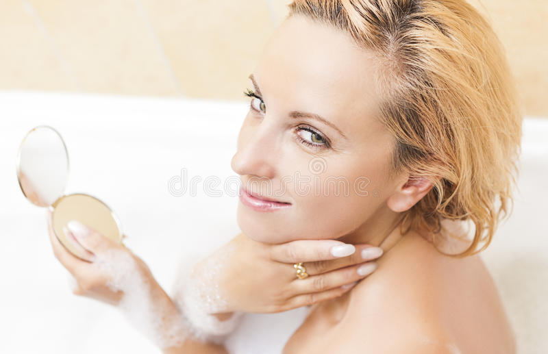 Giovane trucco facente femminile biondo caucasico durante il bagno del processo Espressione facciale positiva Procedura di tratta fotografia stock