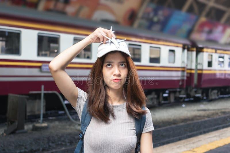 Giovane turista asiatico attraente di signora con l'aeroplano di modello alla stazione ferroviaria Concetto di stile di vita di v fotografia stock libera da diritti