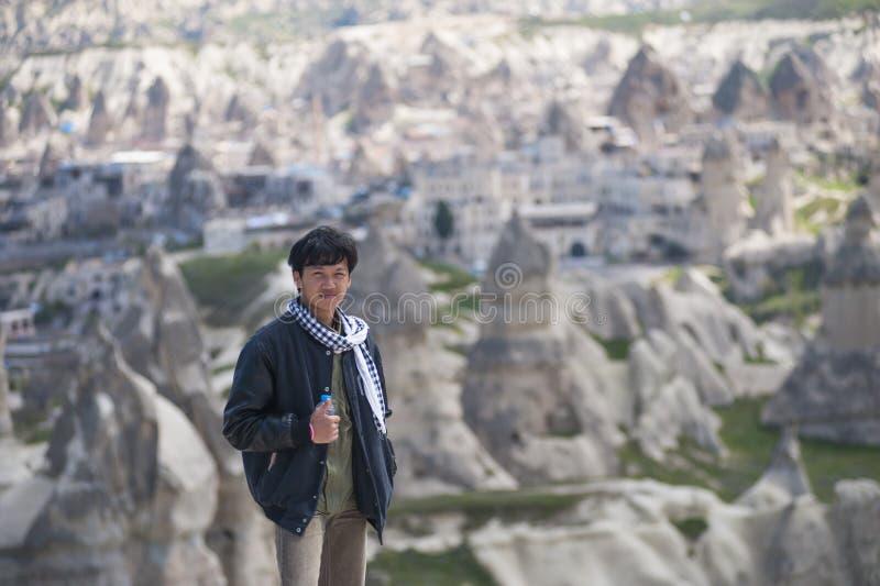 Giovane turista asiatico dell'uomo sulla cima della montagna a Cappadocia fotografie stock libere da diritti