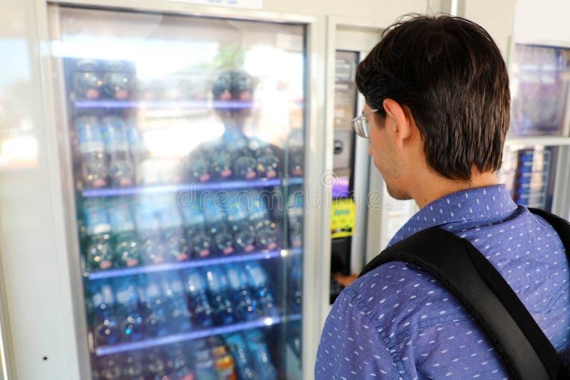 Giovane turista di backpacker scegliere uno spuntino o bere alla macchinetta Macchina di vagliatura con l'uomo fotografie stock