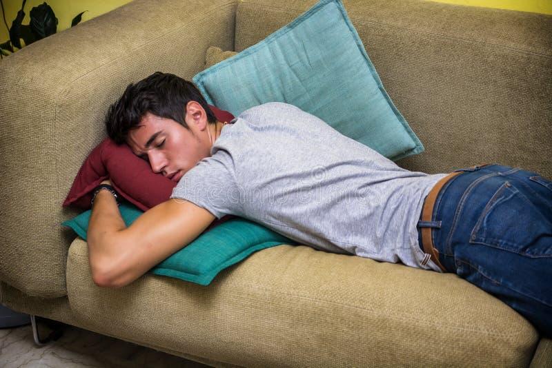Giovane ubriaco che dorme sullo strato del salone fotografia stock