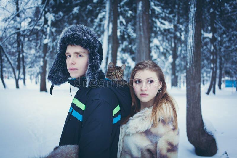 Giovane in un cappello di pelliccia con un earflap con un gattino nel cappuccio del suo rivestimento e di una ragazza in una pell fotografia stock