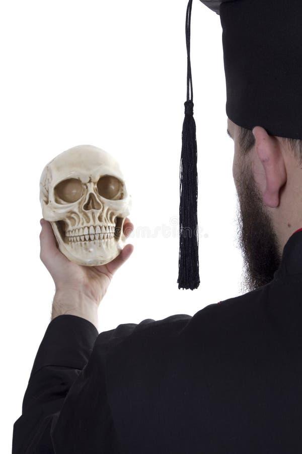 Giovane in un cappello laureato con un cranio fotografia stock
