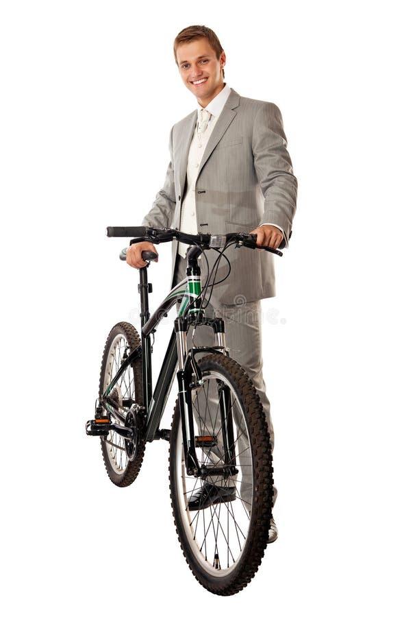 Giovane in un vestito che si leva in piedi vicino ad una bici fotografia stock libera da diritti