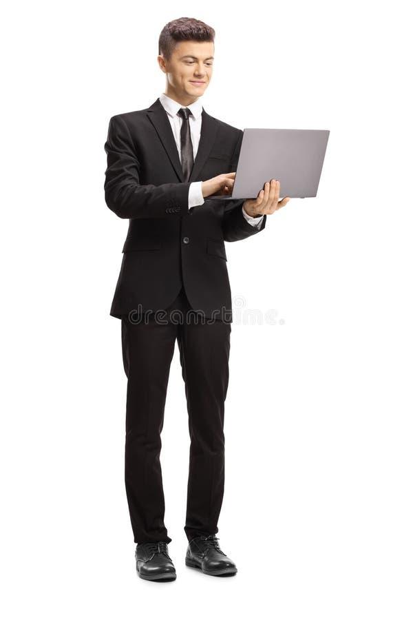 Giovane in una condizione del vestito e scrivere su un computer portatile fotografia stock