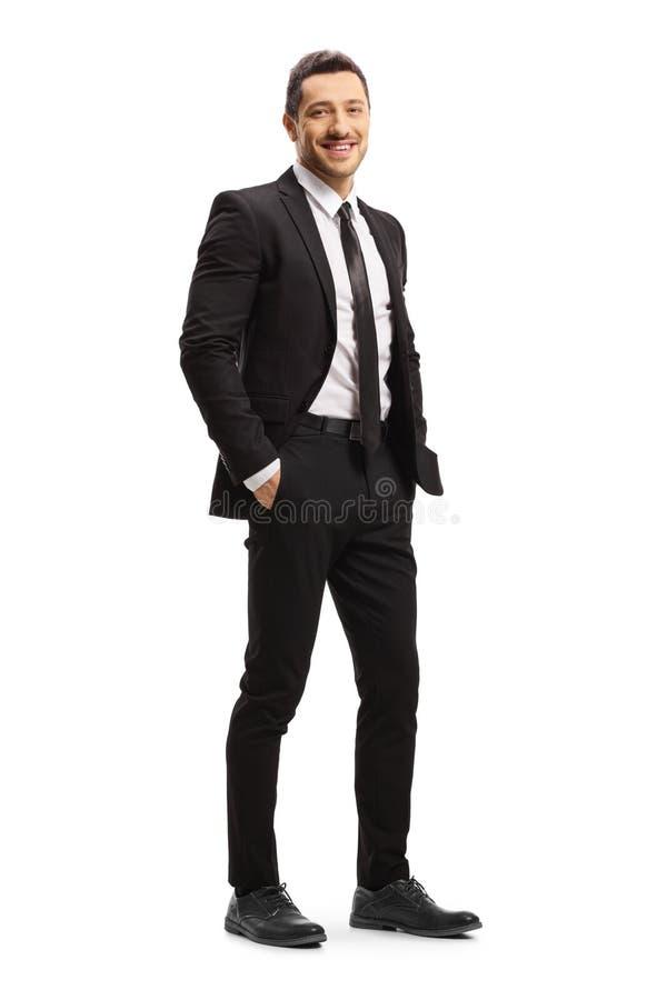 Giovane in una posa nera del vestito fotografia stock