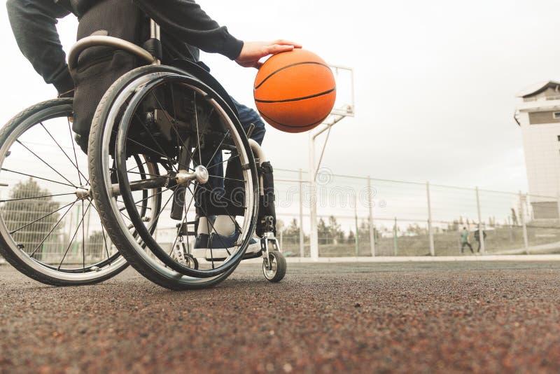 Giovane in una sedia a rotelle che gioca pallacanestro immagine stock