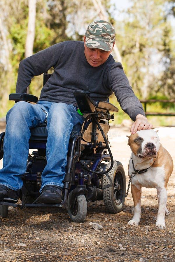 Giovane in una sedia a rotelle con il suo cane fedele. fotografia stock libera da diritti