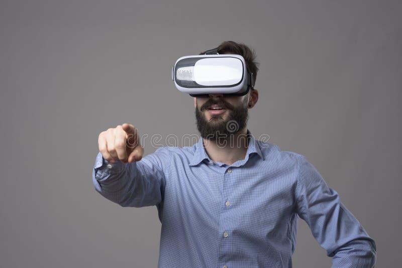 Giovane uomo adulto barbuto stupito di affari con la cuffia avricolare del vr che tocca touch screen digitale virtuale immagine stock libera da diritti