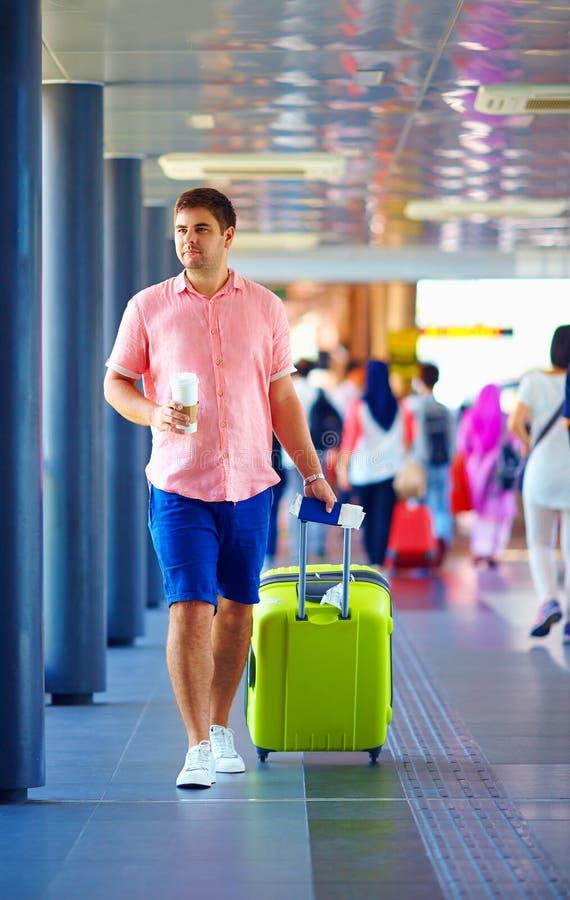 Giovane uomo adulto che cammina attraverso l'aeroporto internazionale ammucchiato fotografia stock