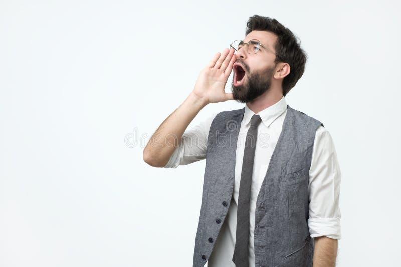 Giovane uomo adulto ispanico con la barba che grida alto e che grida per parteggiare per la mano sulla bocca fotografie stock
