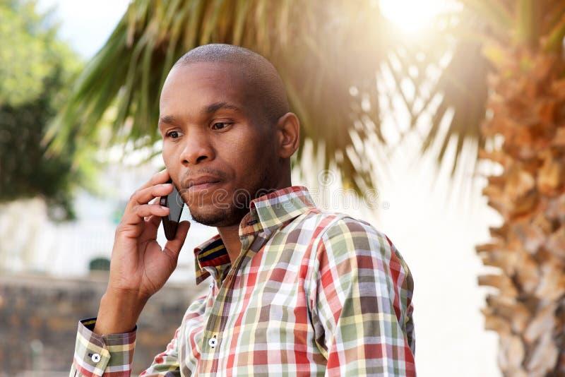 Giovane uomo africano bello che parla sul telefono cellulare fuori fotografie stock libere da diritti