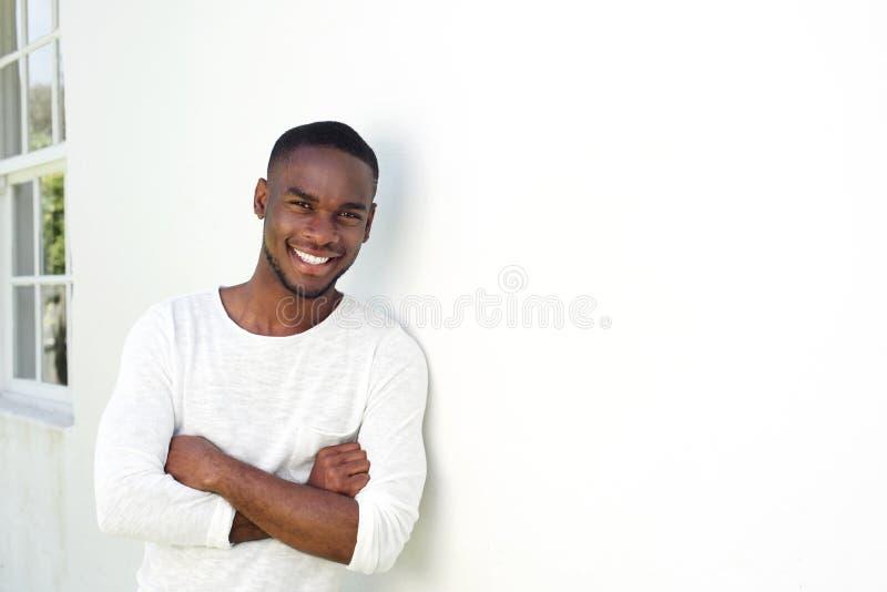 Giovane uomo africano bello che sta con le sue armi attraversate fotografie stock