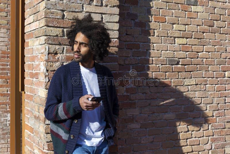Giovane uomo africano bello facendo uso del suo smartphone con il sorriso mentre appoggiandosi un'aria aperta bricked della paret immagini stock