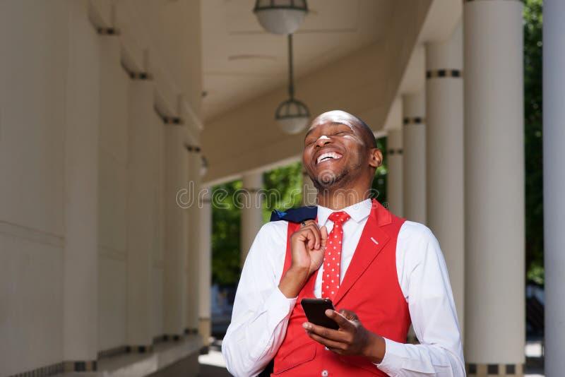 Giovane uomo africano bello in vestito che ride all'aperto con il cellulare immagine stock