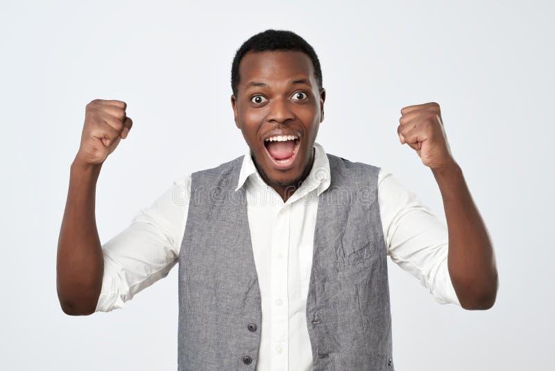Giovane uomo africano che celebra vittoria sopra fondo grigio fotografia stock libera da diritti