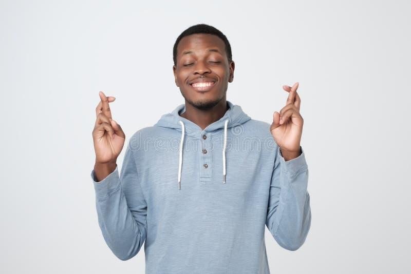 Giovane uomo africano che fa un desiderio isolato sul fondo bianco fotografia stock