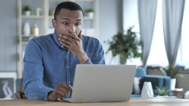 Giovane uomo africano colpito e sgomento che si domanda e che lavora al computer portatile fotografia stock