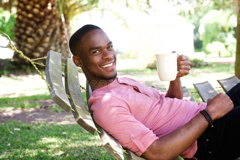 Giovane uomo africano con un caffè che si rilassa sull'amaca immagine stock libera da diritti