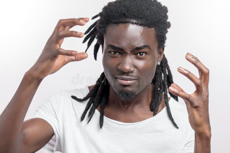 Giovane uomo africano emozionale con i dreadlocks che stanno isolati sopra bianco sguardo della macchina fotografica fotografia stock