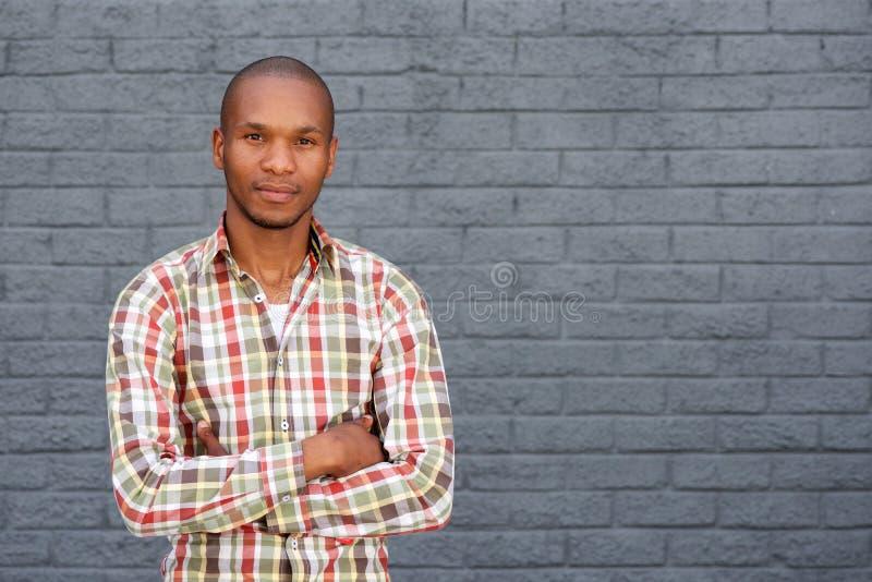 Giovane uomo africano fresco che fa una pausa parete grigia con le armi attraversate immagine stock libera da diritti