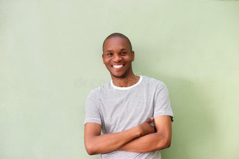 Giovane uomo africano sorridente che sta contro la parete verde fotografie stock