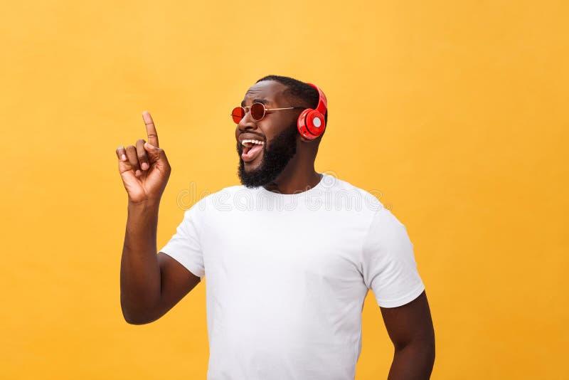 Giovane uomo afroamericano bello che ascolta e che sorride con la musica sul suo dispositivo mobile sopra giallo immagine stock libera da diritti