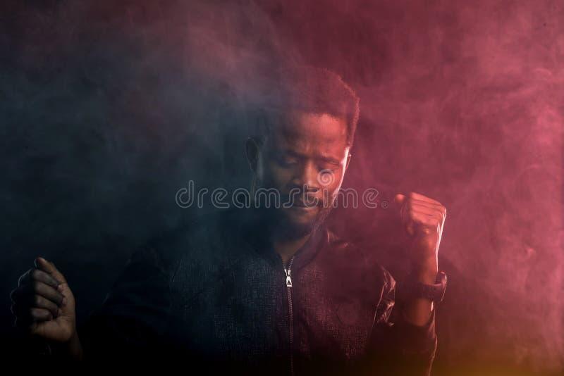 Giovane uomo afroamericano bello che balla nello scuro immagini stock