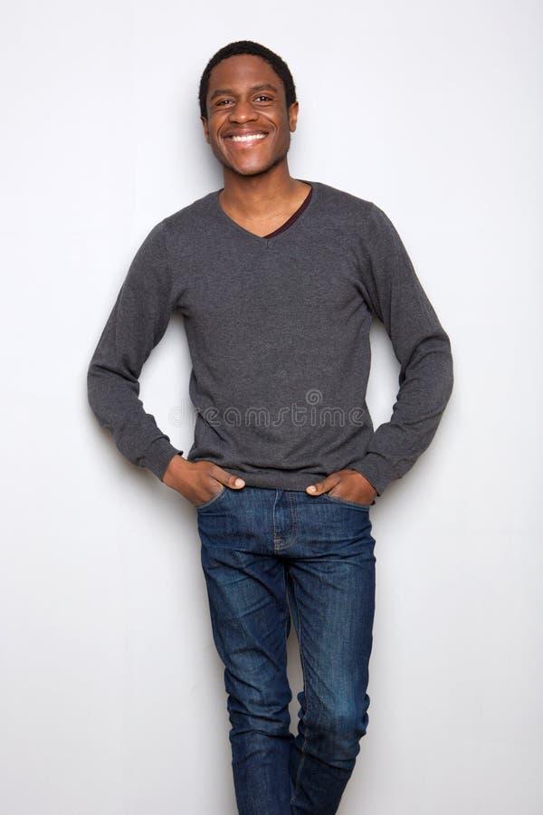 Giovane uomo afroamericano bello che sta contro il fondo bianco fotografia stock