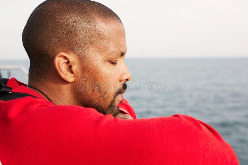 Giovane uomo afroamericano bello dei pantaloni a vita bassa che sogna sulla spiaggia con gli occhi chiusi Ritratto del primo pian fotografie stock