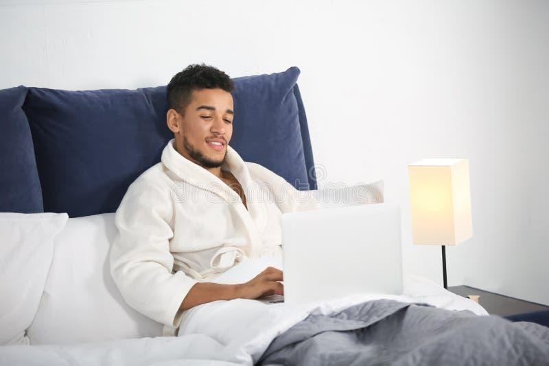 Giovane uomo afroamericano con il computer portatile che riposa a letto immagini stock libere da diritti