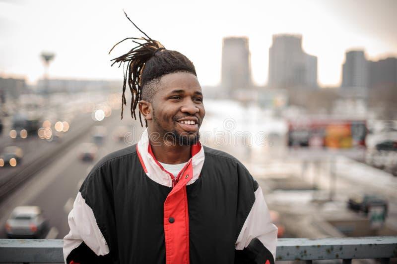 Giovane uomo afroamericano sorridente che sta sui precedenti del ro immagini stock