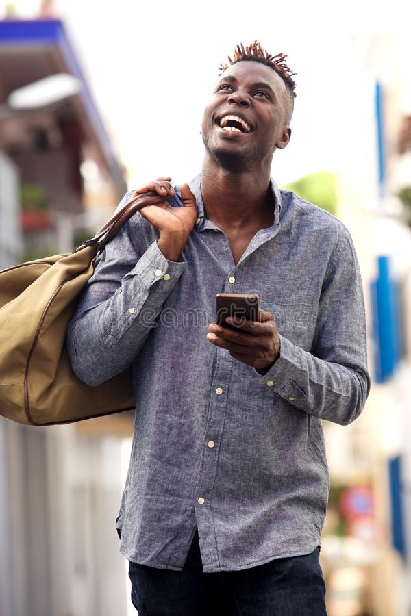 Giovane uomo afroamericano sorridente con la borsa che cammina fuori con il telefono cellulare immagine stock libera da diritti