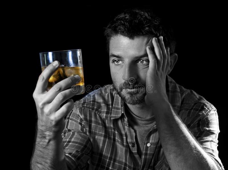 Giovane uomo alcolico della persona dedita potabile con il vetro del whiskey nel concetto di alcolismo immagini stock libere da diritti