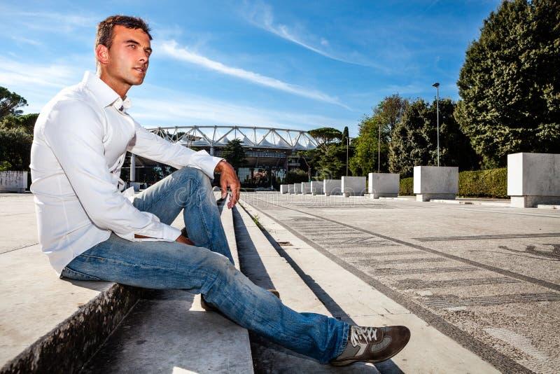 Giovane uomo alla moda all'aperto Sedendosi sui punti immagine stock