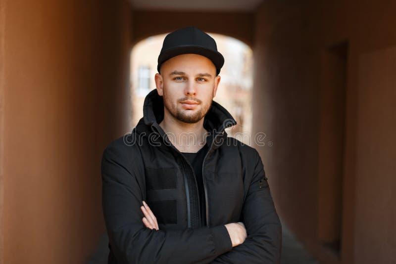 Giovane uomo alla moda bello dei pantaloni a vita bassa in un berretto da baseball nero fotografia stock