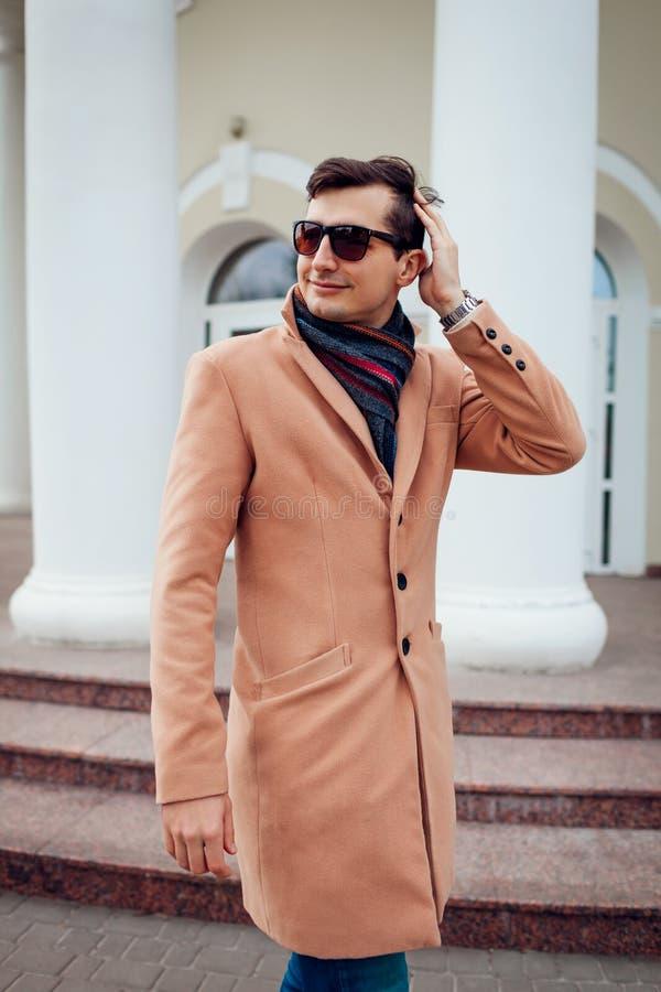 Giovane uomo alla moda che cammina nella città Tipo bello che indossa i vestiti e gli accessori classici Modo della via immagine stock libera da diritti