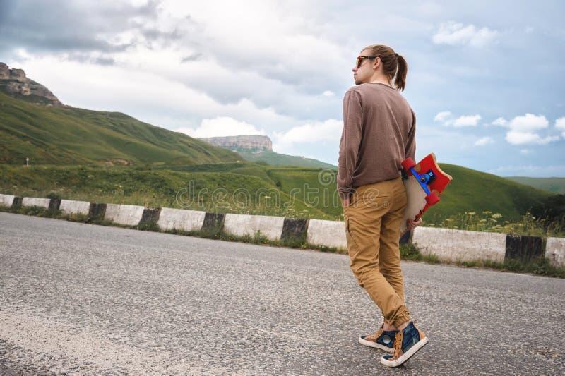 Giovane uomo alla moda dei pantaloni a vita bassa con capelli lunghi ed in occhiali da sole che cammina con un longboard in sue m fotografie stock